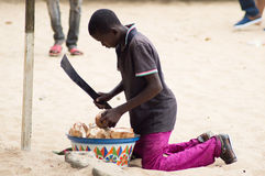 Child labor. Abidjan, Ivory Coast - 29 August 2015: a young boy, machete in hand size a drowning coconut to sell it to a customer Stock Photos