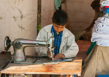 Child labor, boy sewing in booth on the market. Royalty Free Stock Image