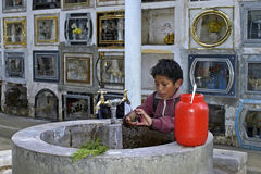 Child labor on cemetery of the city Cochabamba. Bolivia, working Bolivian, Indian, boy among the gravestones. Given the poverty and high unemployment there is Royalty Free Stock Photos