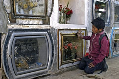 Child labor on cemetery of the city Cochabamba. Bolivia, working Bolivian, Indian, boy among the gravestones. Given the poverty and high unemployment there is Stock Photo