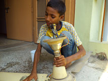Child Labor. Minor child from India cleaning a ceiling fan with a wet cloth Stock Photo