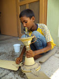 Child Labor. Minor child from India cleaning a ceiling fan with a wet cloth Stock Photography