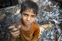 A child labor showing unmaking steel spoon.