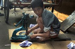 Child Labour in India. An Indian child labour is working in with a small hand machine on the road just in front of a small scale factory. Due to shortage of Royalty Free Stock Image