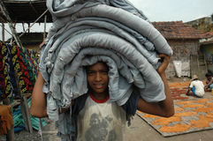 Child Labour In India. DILA RAM from Bihar state carrying raw leather on his head at the leather factory of Kolkata.His father also a factory labour Stock Photos