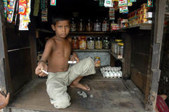 Child Labour In India. Kolkata,West Bengal-India-PINTU  not to go school,doing work in his father's cigarette stall Royalty Free Stock Photo