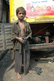 Child Labour In India. Kolkata,West Bengal-India- Nine years old OSTAD (gift name by the public) working on the road side Auto car repairing centre of Kolkata Stock Photo