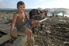 Child Labour Latino boy on landfill Nicaragua. Nicaragua, capital, city Managua: boy is working with horse and wagon, for transporting recycling goods, among the royalty free stock images