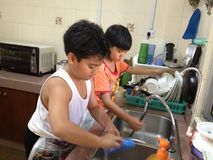 Child labour vs Household Chores. Asian children washing the dishes for Child labour vs Household Chores concept royalty free stock photography