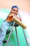 Child on ladder with a roller. Smiling little girl on a ladder with a roller Stock Photography
