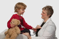 Child with lady doctor. Young caucasian boy and a short hair woman in medical doctor uniform holding a stethoscope on his ear listening to doctor heart beat stock photos