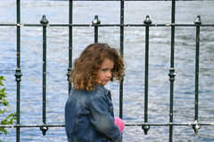 Child by the lake. Child sitting by the lake Royalty Free Stock Image