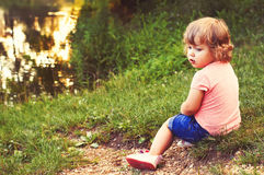 A child on the lake bank. Little girl on the lake shore Royalty Free Stock Photography