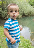 Child beside a lake. Image of a child by a lake looking over the camera Royalty Free Stock Images