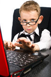 Child and a laptop. Kid in glasses like a big-boss Royalty Free Stock Photography