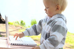 Child with laptop. Small child pressing the button on laptop Stock Photos
