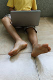 A child with laptop. A boy with laptop sitting on the floor Stock Photos