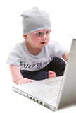 Child at laptop. Child sitting at a laptop studio shoot isolated on white with shadows including path Stock Images