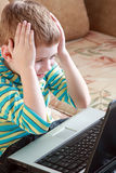The child with laptop. The boy thoughtfully lays on a sofa near a laptop Stock Photo