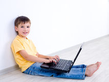 Child with laptop in empty room Stock Photo