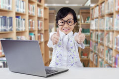 Child with laptop giving thumbs up in library Stock Image