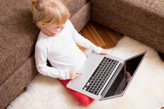 Child  with laptop in her lap Stock Photo