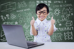 Child with laptop shows OK gesture in class Stock Photos