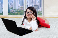 Child with laptop thinks idea on carpet. Cute little girl lying on the carpet with a laptop computer and thinks idea near the apartment window Stock Photos