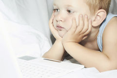 Child with laptop. 4 years old boy watching computer Stock Photos