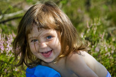 Child laugh. Charmed little girl relaxing in the grass and laughing Stock Photography
