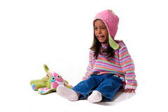 Child laughing. Color image of girl sitting with stuffed animal aughing. taken in studio using white background Royalty Free Stock Photos