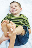 Child laughing barefeet fingers tickling. Little boy getting feet tickled by hands foreground Stock Image