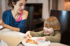Child laughing eating pizza with mother Royalty Free Stock Photography