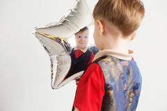 Child laughing looking at the reflection in a distorted mirror. Boy grimacing and playing the ape with star-shaped balloons in studio. Kid looks and rejoices at Stock Photography