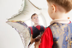 Child laughing looking at the reflection in a distorted mirror. Boy grimacing and playing the ape with star-shaped balloons in studio. Kid looks and rejoices at Royalty Free Stock Photos