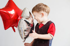 Child laughing looking at the reflection in a distorted mirror. Cute little boy playing with star-shaped balloons in front of white background. Kid looks and Stock Photo