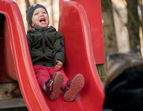 Child laughing loudy sitting on a slide stock images