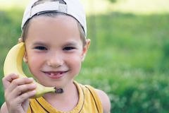 Child laughing while playing pretend with a wooden banana phone. Funny games royalty free stock images