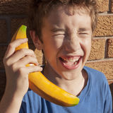 Child Laughing Pretend Play. Child laughing while playing pretend with a wooden banana phone Stock Images