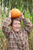 Child laughing with a pumpkin Royalty Free Stock Images
