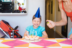 Child laughing and woman hand lighting candles on birthday cake. Three years old blonde child looking laughing and women hand lighting candles with lighter on royalty free stock photography