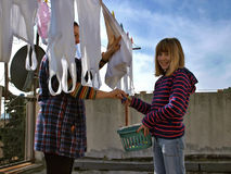 A child and laundry. Young daughter (child) help mother to hanging (laundry) out the washing white clothes - reaching which hangs to dry in a summer breeze on a stock photo
