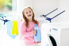 Child in laundry room with washing machine Stock Photo