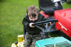Child on lawn mower. Portrait of young boy riding lawn mower on green grass stock image