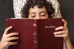 Child laying down and reading the holy bible Stock Photo