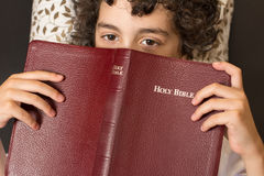 Child laying down and taking a break from reading the holy bible