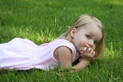 Child laying on grass. Looking with hands on chin royalty free stock image