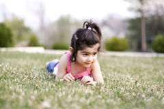 Child laying on grass. Two year old girl enjoying spring weather Stock Image
