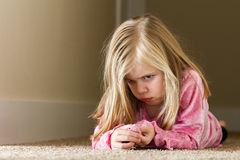 Child laying in the hallway sad Stock Image