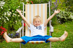 Child laying relaxed in deck chair in summer Royalty Free Stock Images